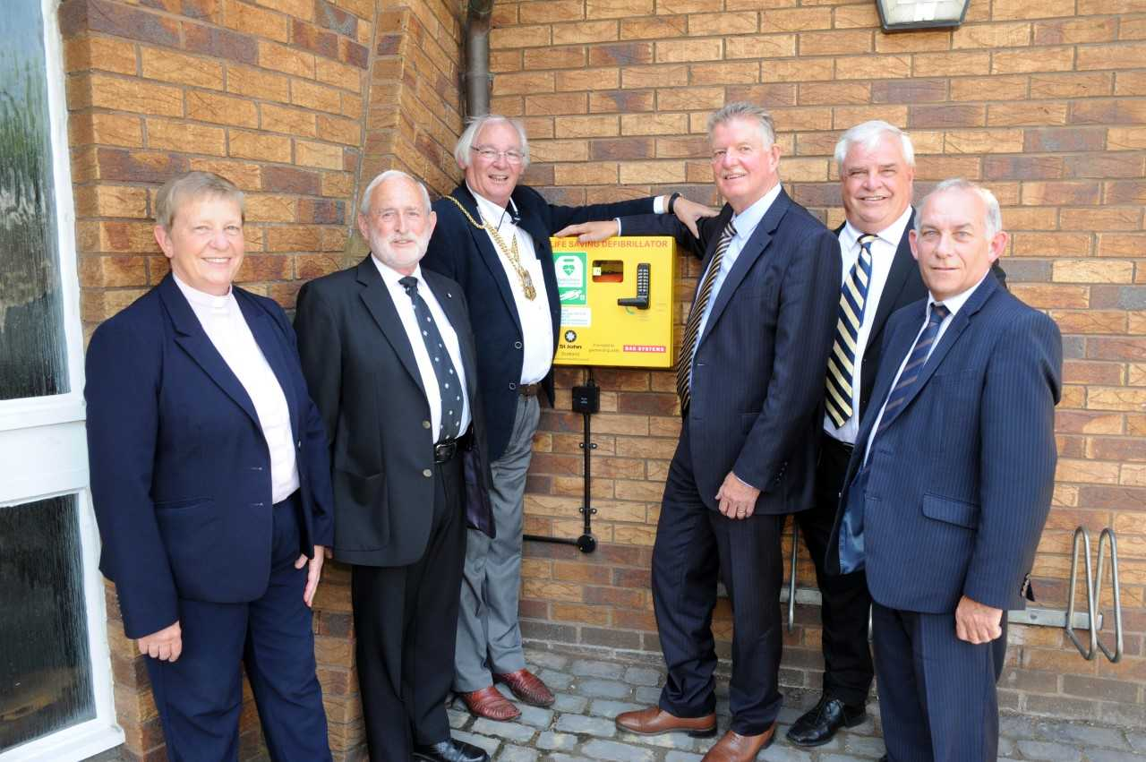 Fife Provost Jim Leishman, Reverend Christine Sime, BAE chiefs and members of St John Scotland's Fife with the new defibrillator in Dalgety Bay. Photo: David Wardle.
